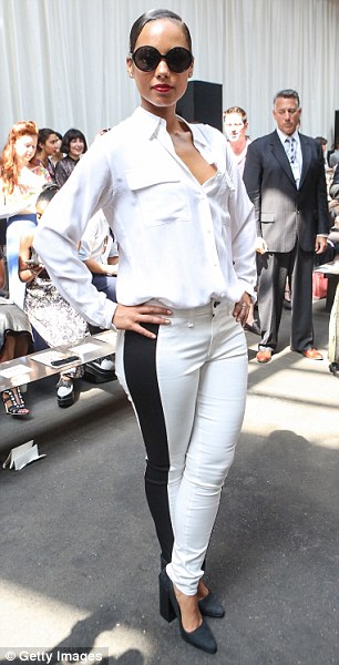 Alicia Keys made a stylish statement in an edgy black and white ensemble at New York Fashion week. She wore a white blouse paired with form-fitting white jeans with black tuxedo stripes down the sides. She completed the looked with black platform pumps, matching shades and wore her newly cut hair slicked back. Read more: http://www.dailymail.co.uk/tvshowbiz/article-2200479/Talk-tents-Alicia-Keys-white-hot-edgy-monochrome-ensemble-New-York-Fashion-Week.