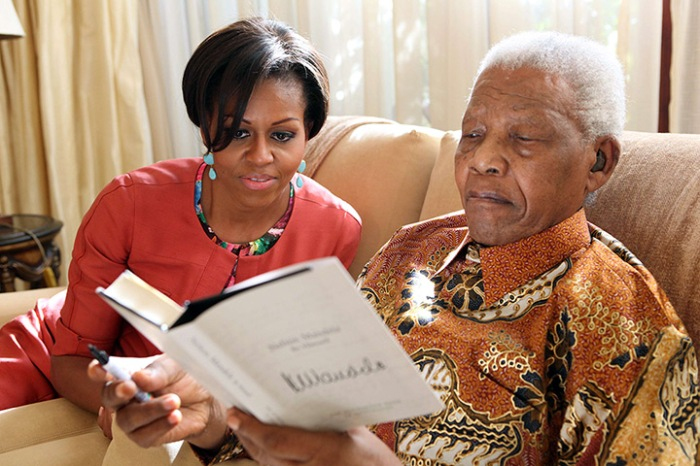 June 21, 2011: Nelson Mandela shows a book to First Lady Michelle Obama at