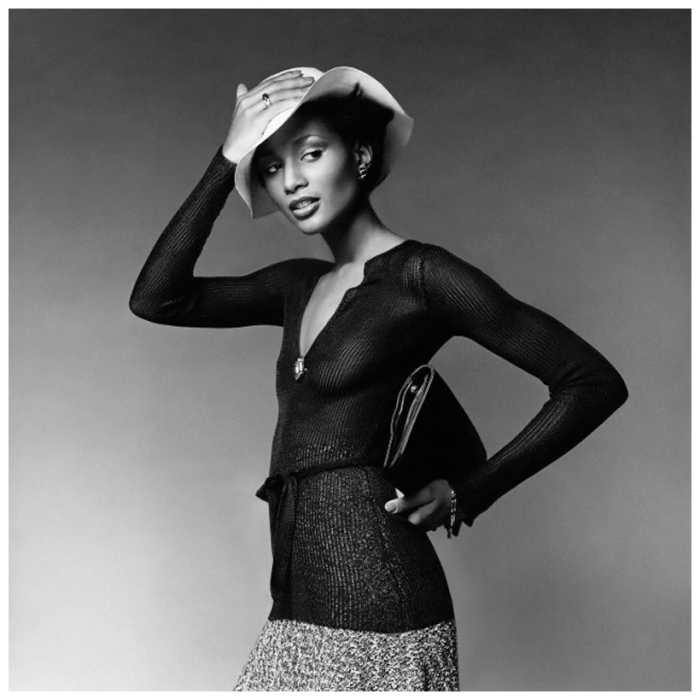 1974-nyc-usa-model-beverly-johnson-wearing-a-sheer-ribbed-pullover-with-low-neck-and-sashed-waist-by-ross-zeldin-a-tweed-knit-flared-skirt-by-scott-barrie-and-holding-a-flat-envelope